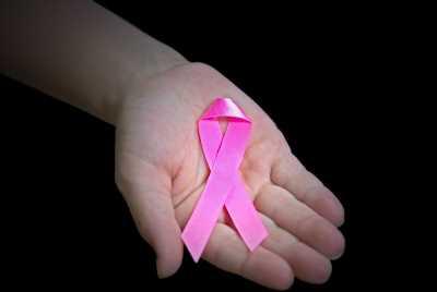 Mão con laço rosa contra o câncer